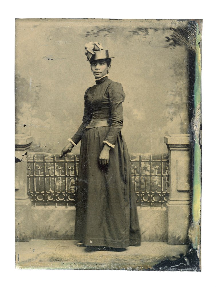 Black-and-white tintype photograph of an African-American woman in 19th century dress standing in front of a fence, taken between 1855-1900