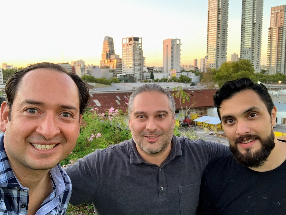 Three men smile at the camera with a city skyline backdrop behind them.