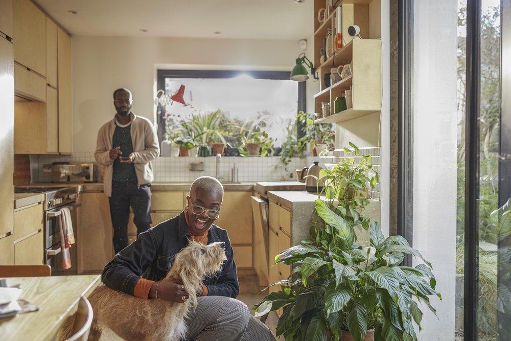 Auf dem Bild sieht man einen Mann, der in der Hocke ist und einen Hund im Arm hält.