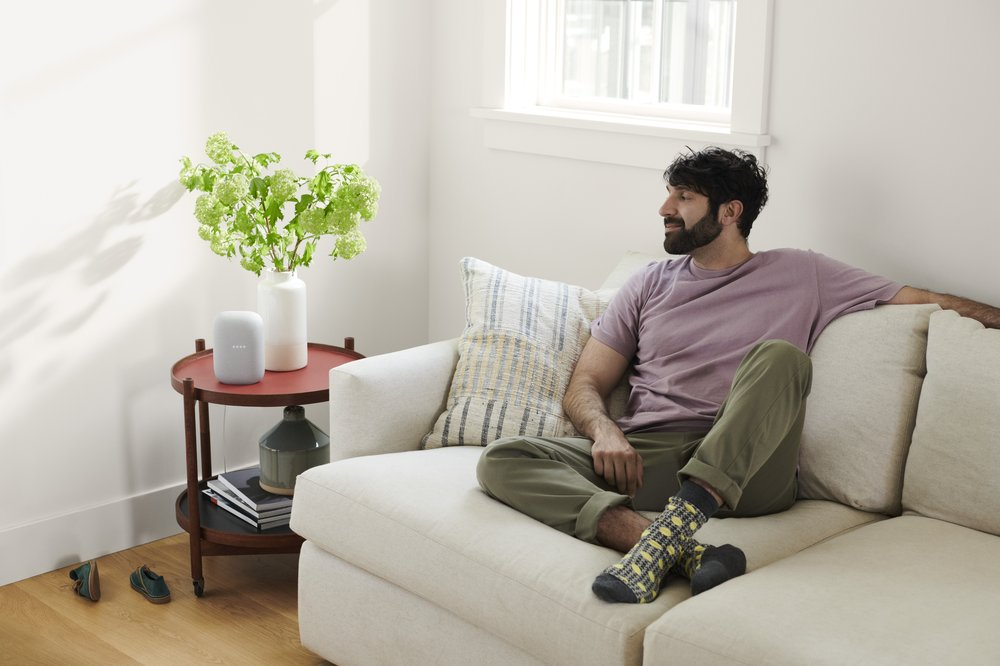 Image shows a man sitting on a white couch in a living room next to a window. On the side table there is a potted plant as well as a Nest Audio.