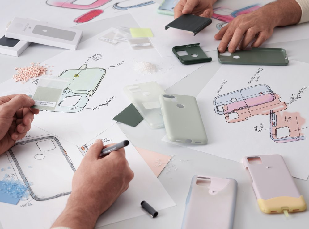 A photo shows the hands of two designers, holding the inner layer of phone case prototypes, working on product sketches and comparing materials.