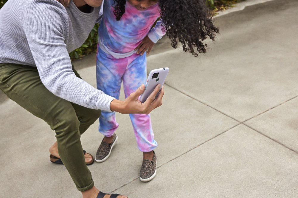 An owner of a Pixel 5a with 5G and the Partially Pink case, takes a selfie with a child.