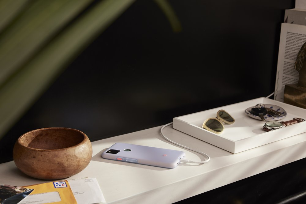 A Pixel 5a with 5G lays display side down, on a shelf alongside a bowl, sunglasses, and other small items. The device is covered by the Partially Pink case.