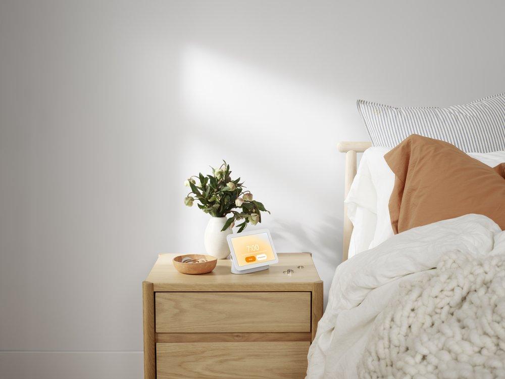 Auf dem Foto ist ein Nest Hub 2nd Gen auf einem Nachttisch zu sehen, der neben einem Bett steht.