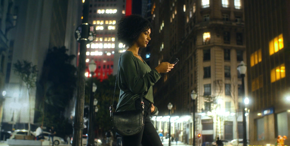 A woman walks on a city street while looking at a mobile phone.