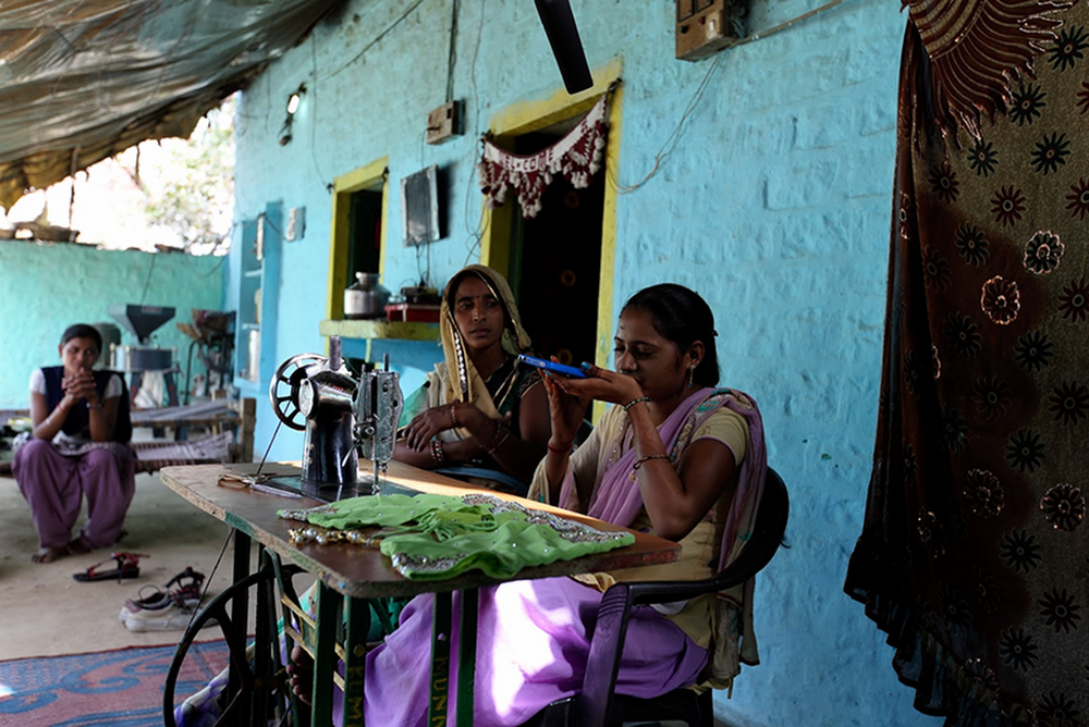 A woman speaks into a phone to search for information. She's sitting alongside another woman — an internet 'saathi', or trainer — a table with a sewing machine on top, in front of a house with walls painted blue and yellow. Another woman watches on in the background.