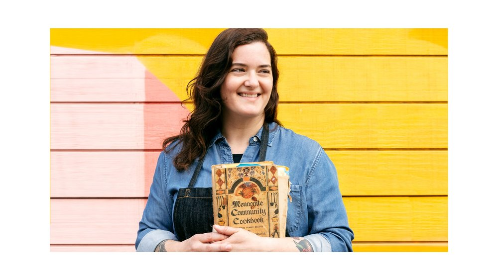 Jo Snyder holds a copy of her cookbook. She is looking beyond the camera, smiling. Her brown hair is down and over her shoulder. She is wearing a denim button-up shirt. She is standing against a yellow and pink wall.