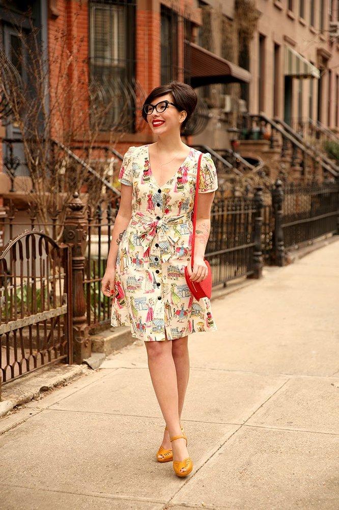 Keiko wears a patterned dress with a handbag.