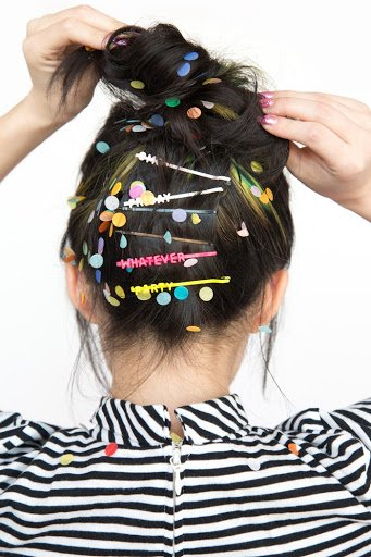 Photo of the back of a woman's head with hair clips that read 'Friday,' 'Whatever,' and 'Party.'