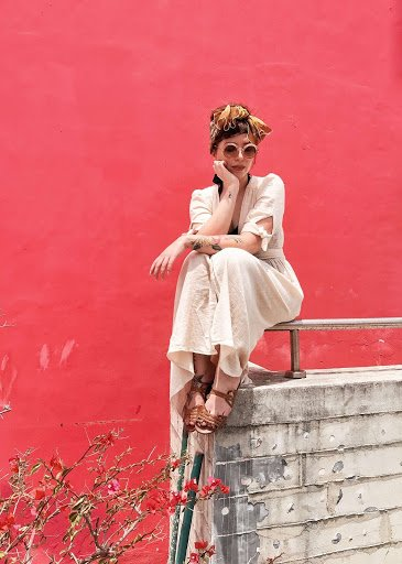 A woman sits on a cement ledge before a red wall.