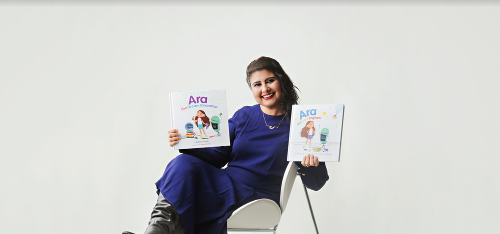 """Photo of Komal Singh sitting on a chair against a white background. She is looking into the camera and smiling, holding a book in each hand. One is """"Ara the Star Engineer"""" and the other is """"Ara the Dream Innovator."""""""