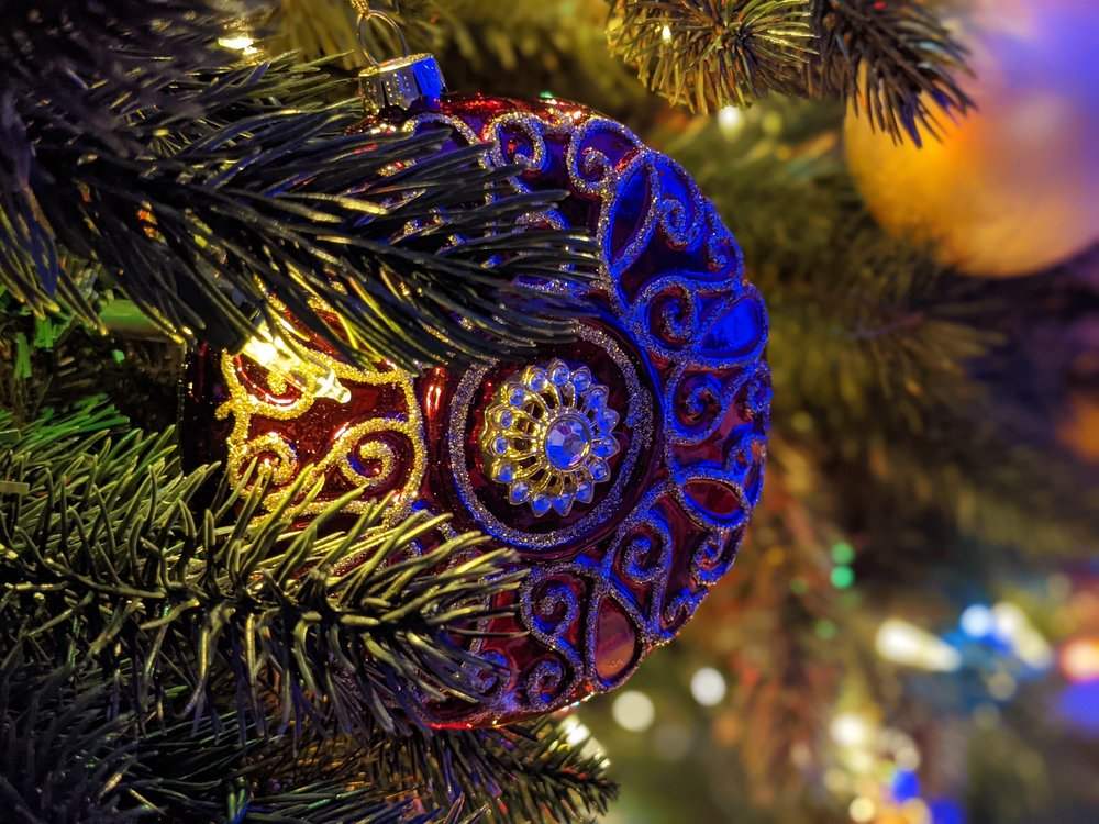 Image showing a macro shot of an ornament hanging in a tree. The lights are low and there is decorative lighting, but the ornament remains in focus while the background is blurry.