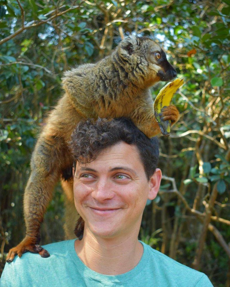 Matt in Madagascar with a furry animal on his head