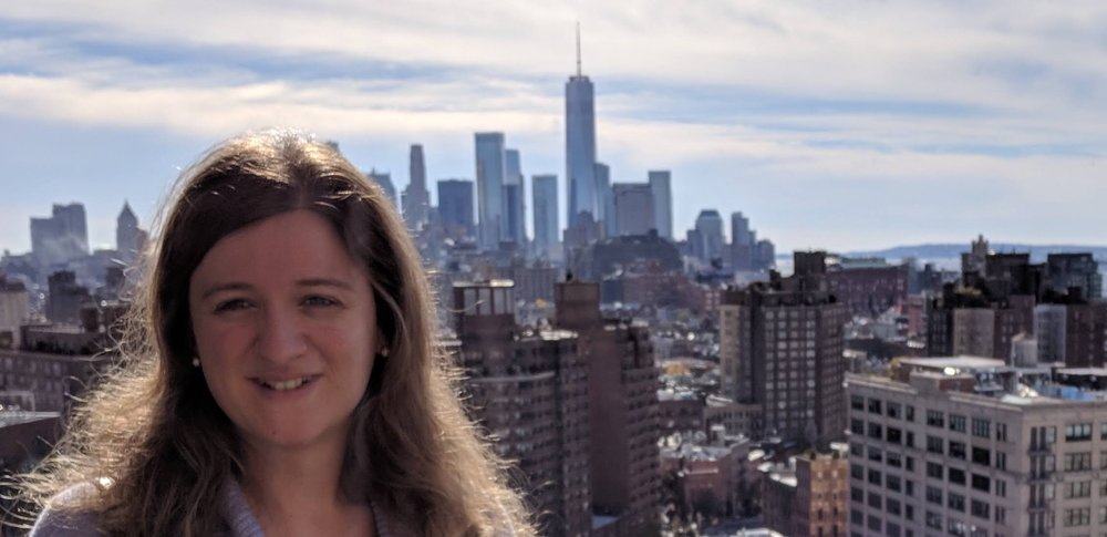 Image of a woman looking into the camera and smiling with a city in the background behind her.