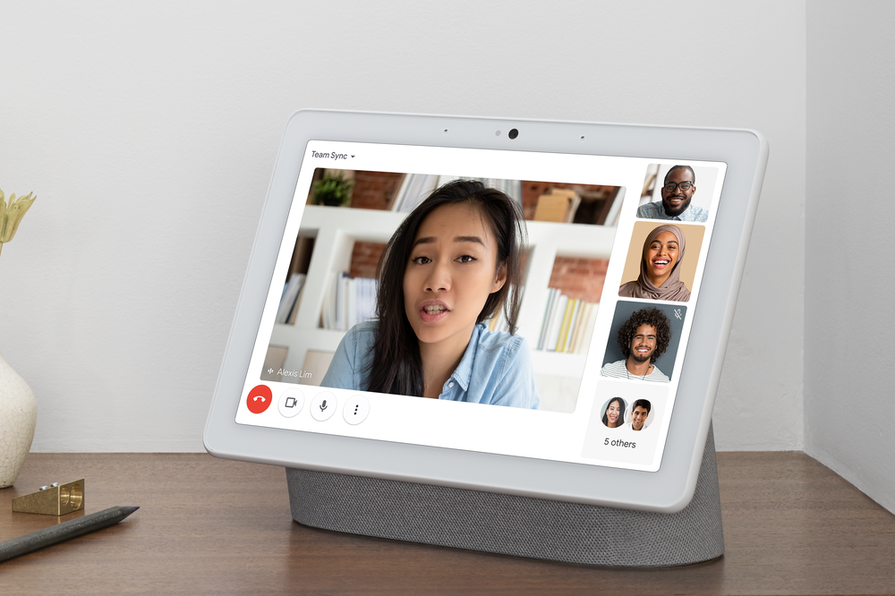 Image shows a women on the screen of a Nest Hub Max having a video call with other coworkers, whose tiles are on the right-hand side of the screen.