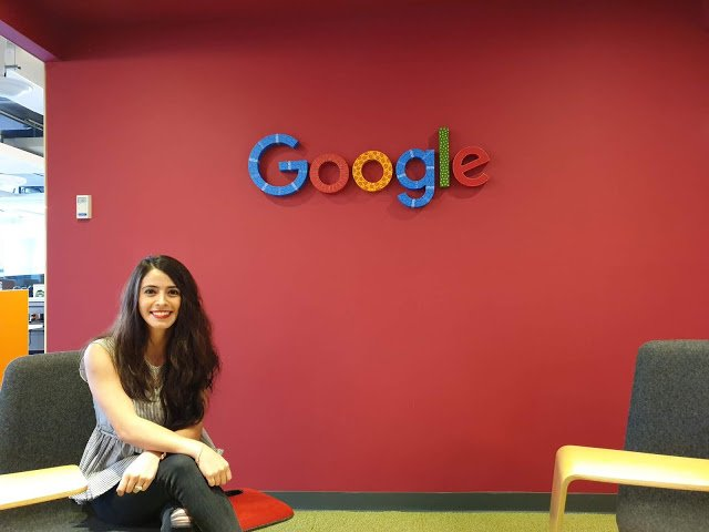 Ana sitting under a Google sign in the office.