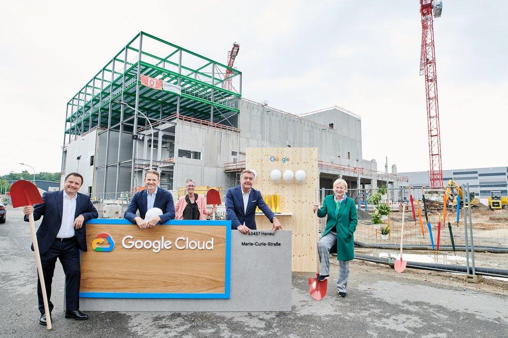 Auf dem Bild sieht man fünf Personen, die vor der Baustelle eines Rechenzentrums in Hanau stehen.