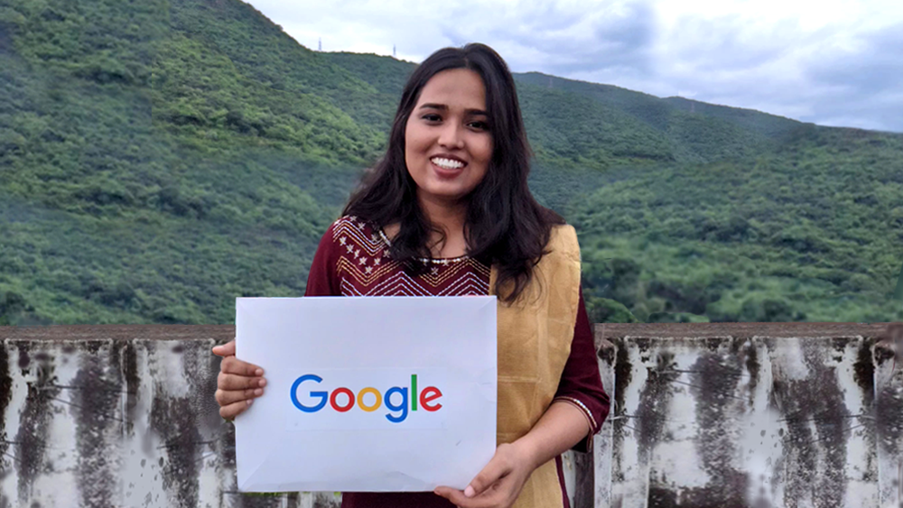 Kiranmayi holds a sign with a Google logo on it. In the background is a stone railing and a view overlooking green hills.