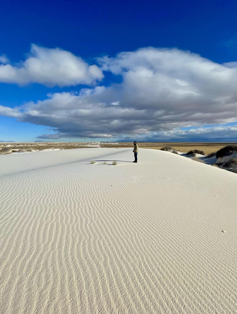 Man standing on sand dunes at White Sands National Park.