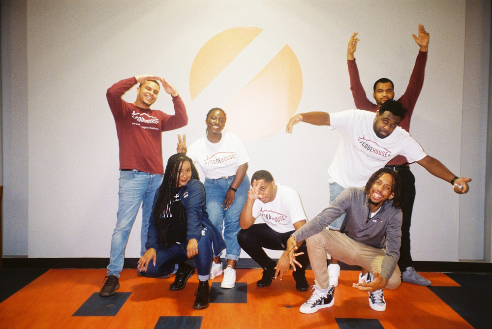 A group of people stand together on an orange rug.