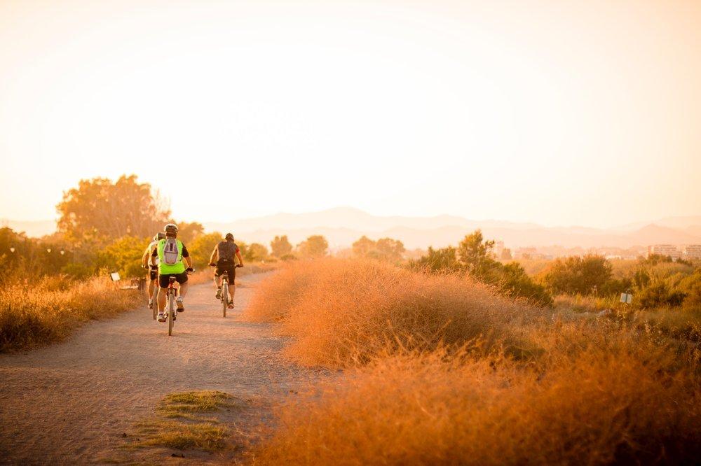 Three bikers riding along a dirt trail.
