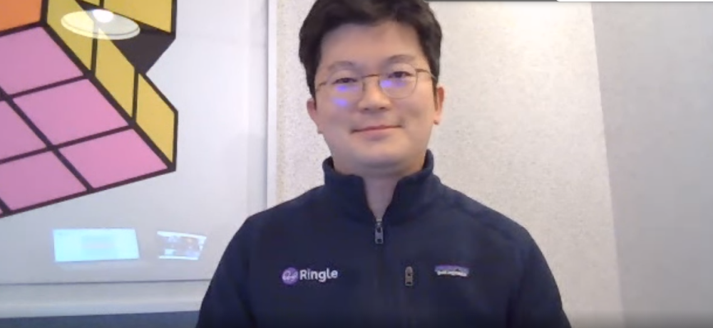 A photo of Ringle founder Seunghoon Lee, looking directly at the camera, wearing a navy jacket with the Ringle logo on.
