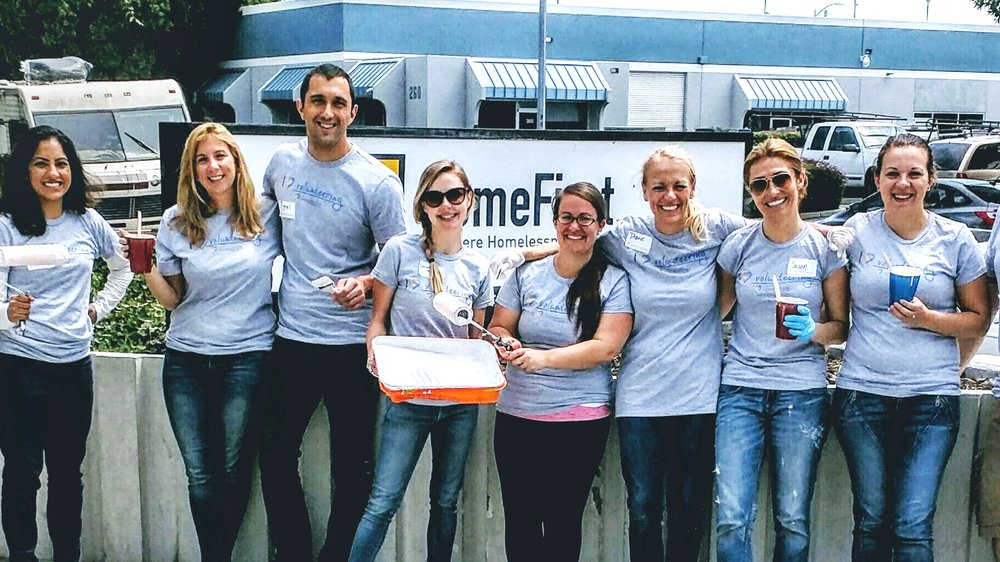 Megan and seven other Googlers stand outside holding paint brushes and cups of paint for a volunteer activity.