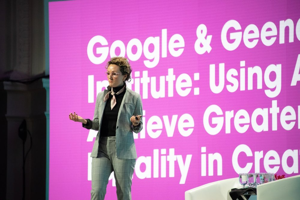 Mackenzie Thomas standing on stage speaking at a Google conference with the Geena Davis Institute.