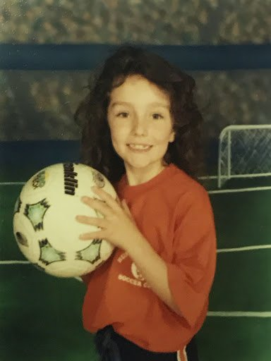 Mackenzie as a young girl wearing a red T-shirt and holding a soccer ball.