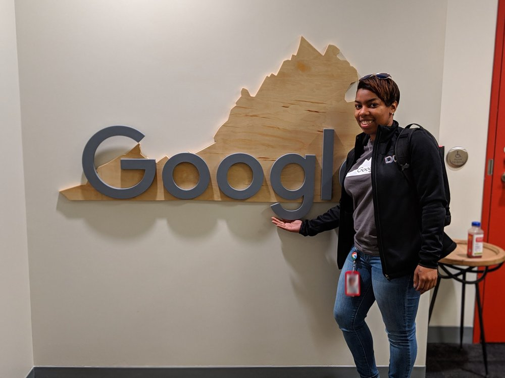 Joy stands in front of a Google logo across a piece of wood cut in the shape of Virginia.