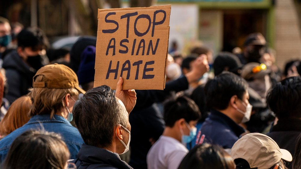 "A ""Stop Asian Hate"" protest sign being held up in a crowd of demonstrators"