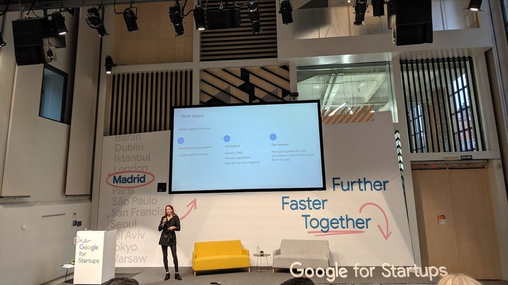 """Hannah stands on stage, speaking into a microphone. In the background is a screen showing presentation slides, mounted on a white wall with the words """"Further Faster Together"""" on the right side, and list of large cities on the left. In front of the wall is a yellow couch and grey couch, and a podium with the Google for Startups logo on it."""