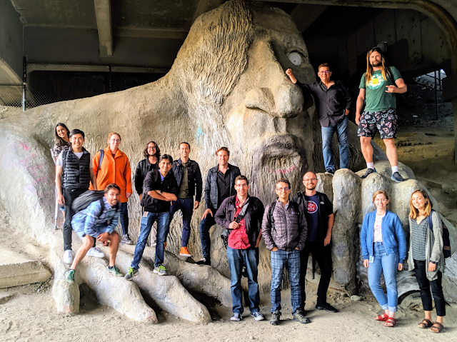 Caile and her teammates standing in front of large statue.
