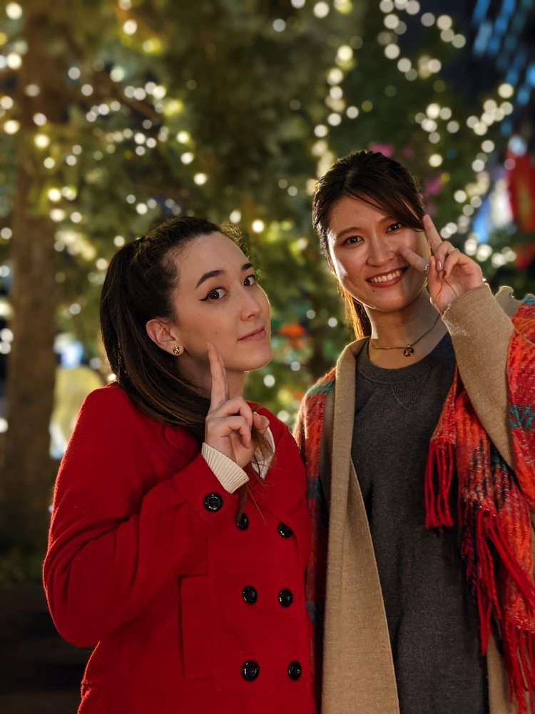 Image showing two women smiling at the camera. They are in focus while the decorated tree in the background is blurry.