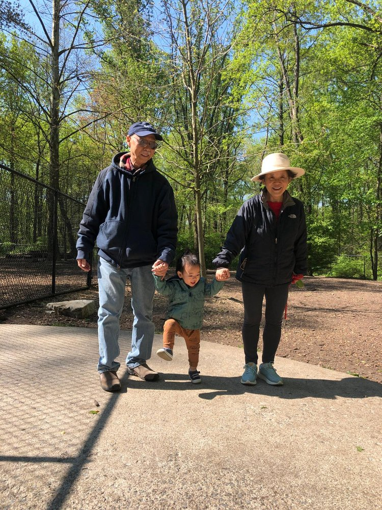 Tony's parents and Owen all holding hands walking down a sidewalk together with trees in the background.
