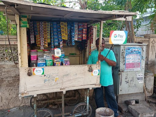 A merchant standing next to a stall on the side of the road in India, with signs indicating that he accepts Google Pay as a payment method.
