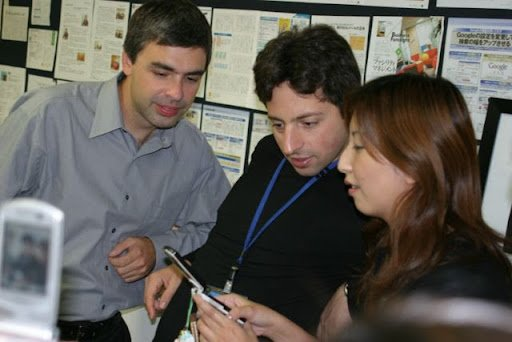 Google's founders Larry Page and Sergey Brin alongside an employee at Google's first Tokyo office. The Googler is demonstrating something on her phone.