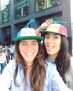 Luisa and teammate, Sarah, posing outdoors with Noogler hats.