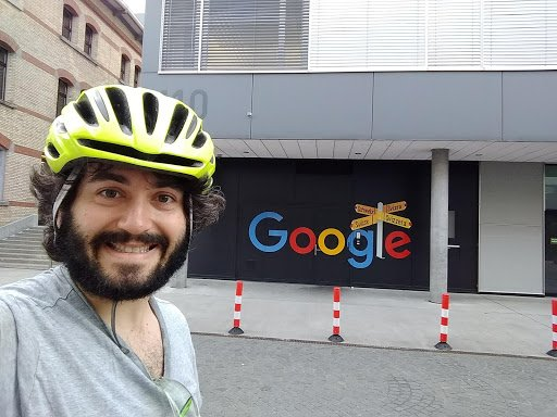 Paul wearing a bike helmet in front of a Google sign.