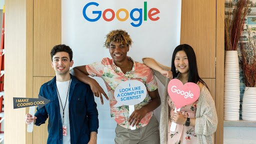 Three students posing in front of Google banner holding props.