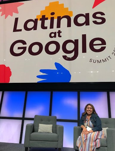 Karina sitting on stage with a presentation behind her with the text Latinas at Google