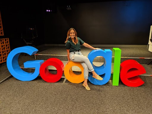 Paola sitting on a large sculpture of the Google logo