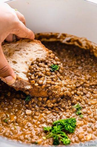 A hand dips a piece of bread into a pot of lentil soup.