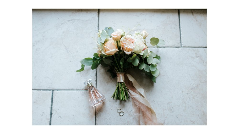 Photograph of a wedding bouquet next to a small bottle of perfume and two rings.