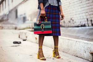 woman-holding-green-and-red-leather-handbag-932401.jpg
