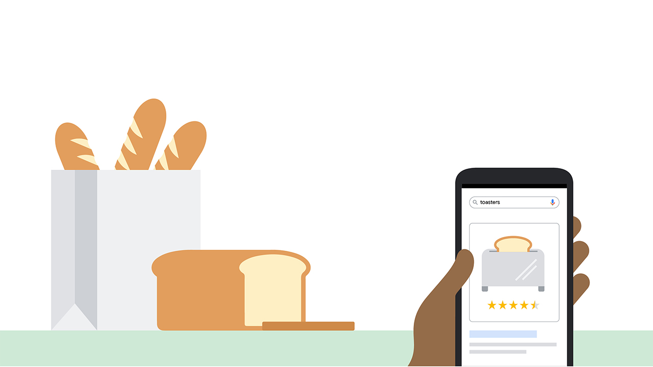 """A hand holding a phone that displays a search results page for """"toasters"""" with an ad for a toaster. In the background is a counter with baguettes and a loaf of bread."""