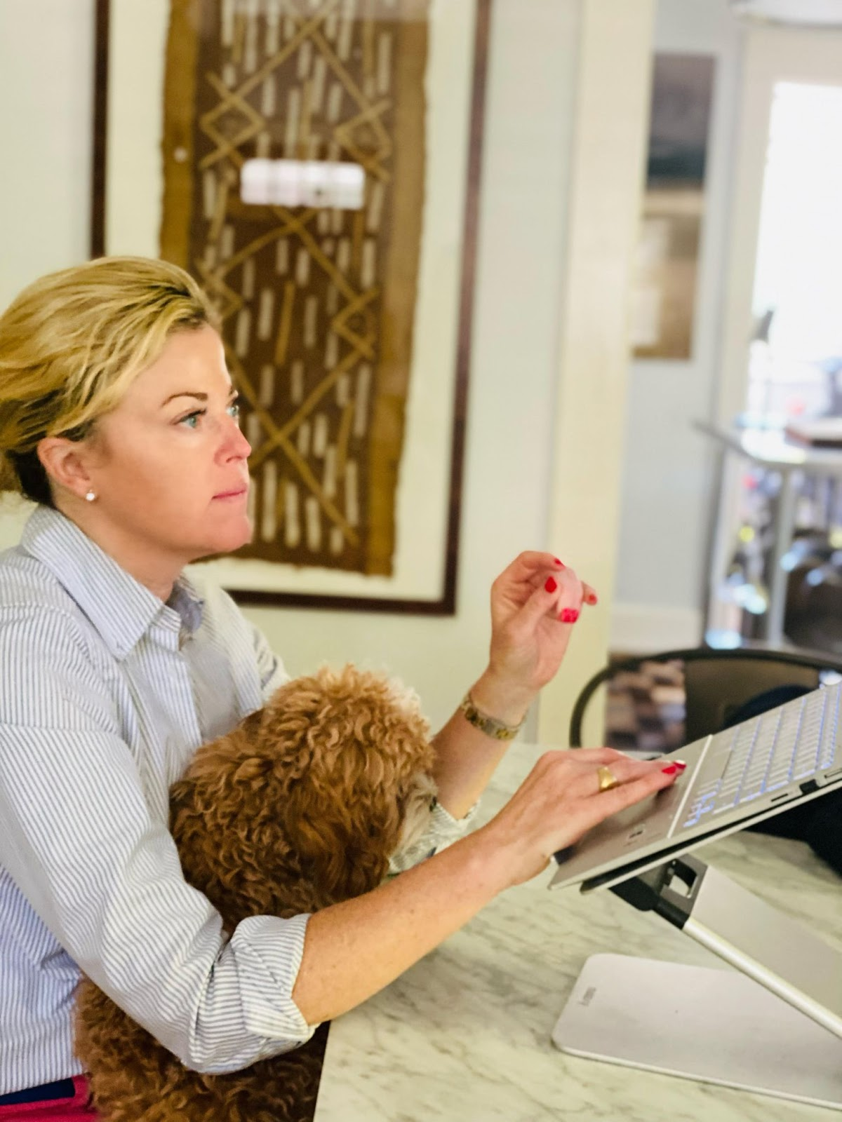 Angela sitting at a table working on a laptop with her fluffy brown puppy in her lap