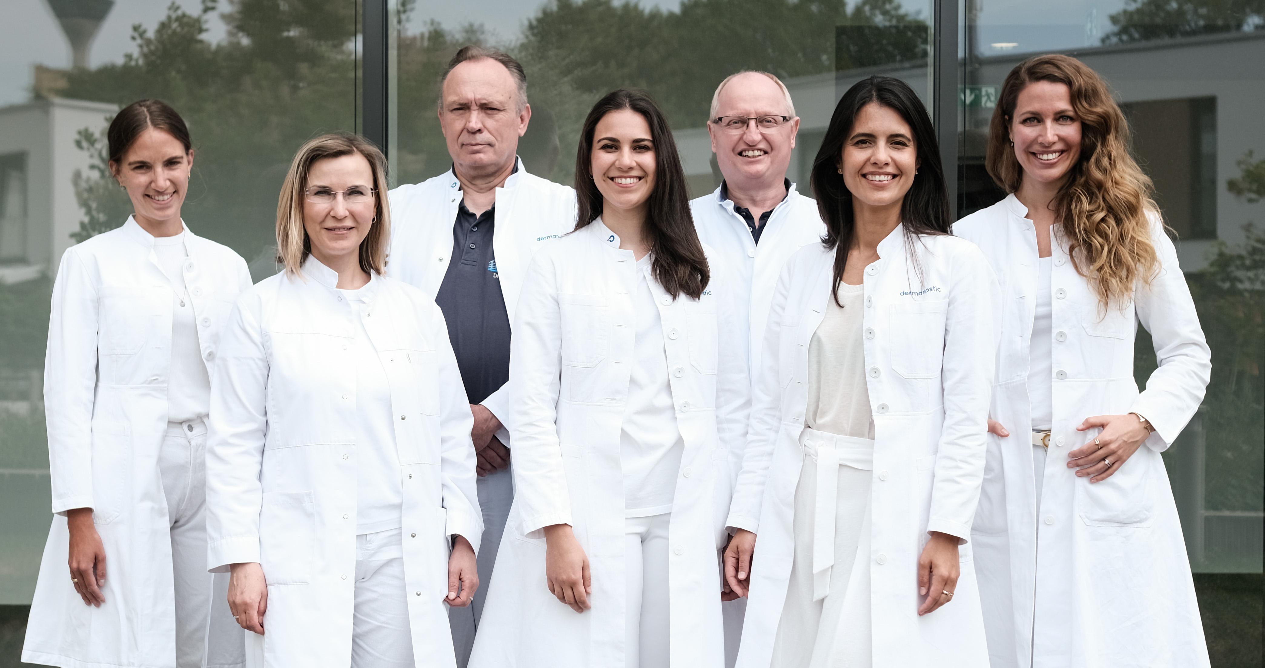 Auf dem Bild ist das dermanositc-Team aus Düsseldorf zu sehen, alle in weiß gekleidet.