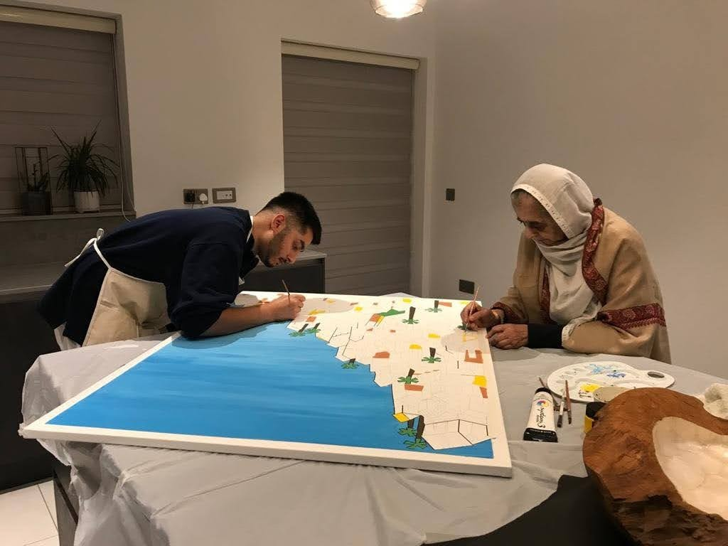 Khalid and his grandmother working on the Rio de Janeiro painting together.