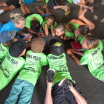 Kamp Kumulani kids on floor in circle with green shirts